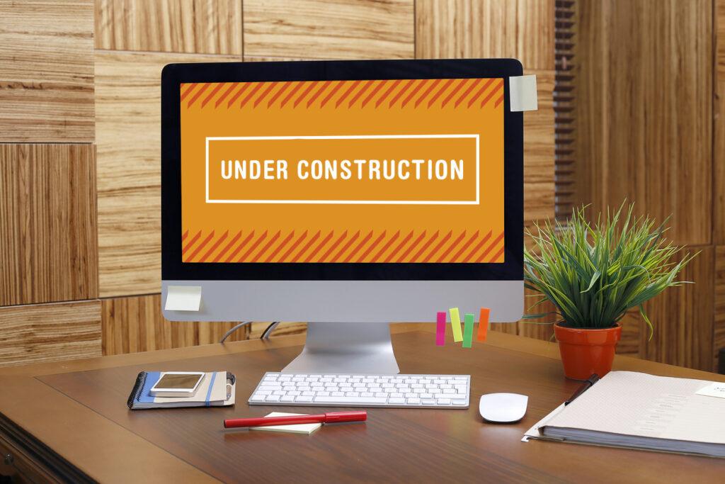 """Scheibtisch mit Bildschirm. Der zeigt eine Seite während eines Webseiten Relaunchs mit einem großen Schild """"Under Construction"""""""