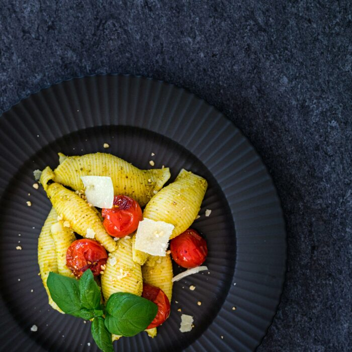 Beispiel für Lebensmittelfotografie: ein schön angerichteter schwarzer Teller mit Pasta, Tomaten und Basilikum
