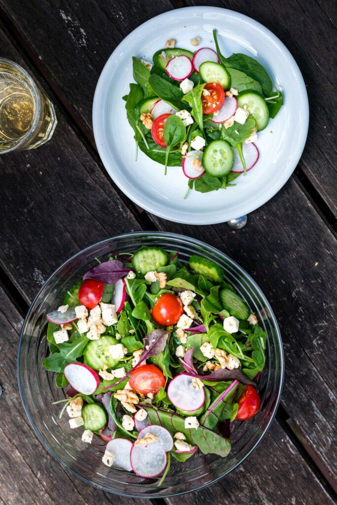 Lebensmittelfotografie: eine Schüssel Salat, daneben ein Teller mit einer Portion des Salats
