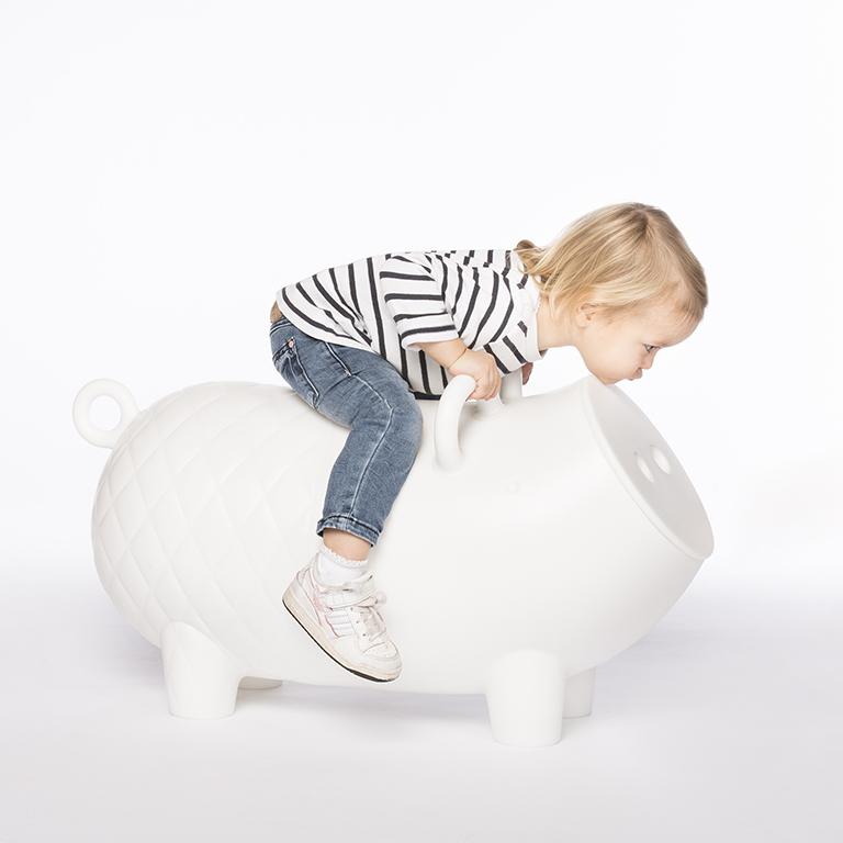 Kinderfotografie zeigt Kind auf einem weißen Designer-Sitzmöbel in Form eines Schweins