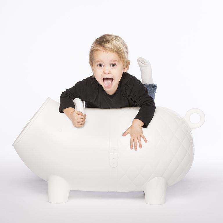 Kindershooting mit Spaßfaktor: Kind liegt auf einem Designer-Sitzmöbel in Form eines Schweins und zieht Grimassen