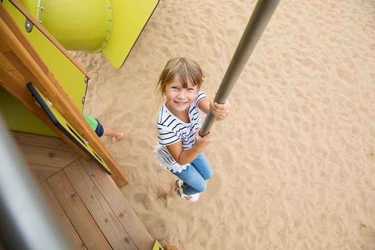 Kinderfotografie mit spannender Perspektive: Blick von oben auf ein Kind, das an einer Stange nach unten rutscht und in die Kamera lacht