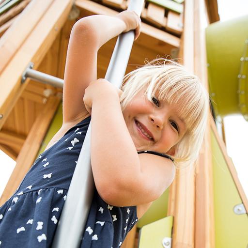 Spaß beim Kindershooting auf dem Spielplatz: Nahaufnahme eines lachenden Mädchens beim Spielen