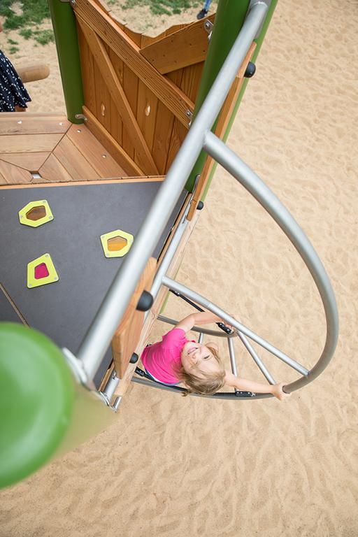 Kinderfotografie wird nie langweilig: Foto von oben, während ein Mädchen an einer Outdoor-Spielanlage klettert