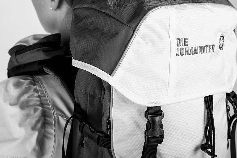 People Fotografie mal in schwarz-weiß: Frau mit einem Rucksack der Johanniter von hinten fotografiert