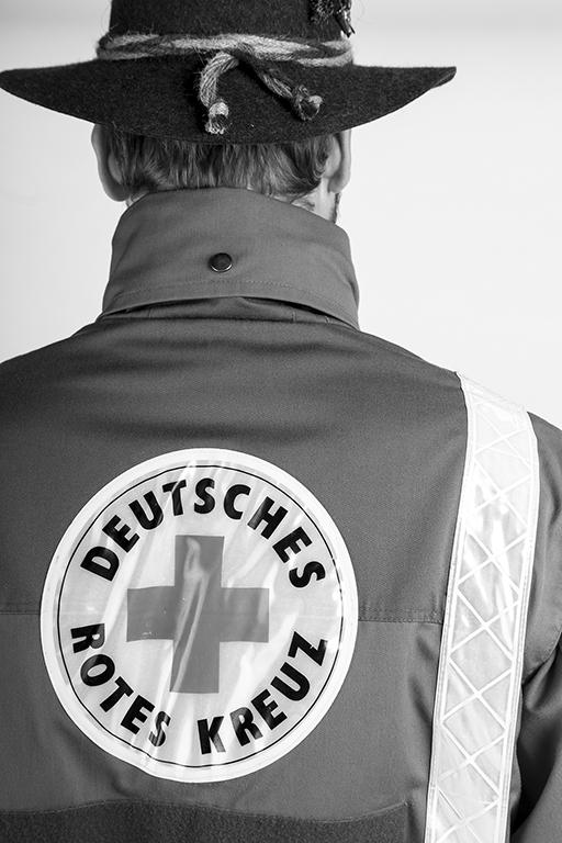 Schwarz-weiß People Fotografie zeigt Freiwilligen vom DRK in Uniform von hinten.