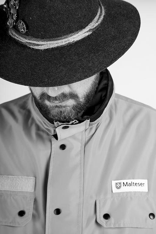 People Fotografie mal in schwarz-weiß: bärtiger Mann in Malteser-Uniform von vorne fotografiert. Dabei neigt er den Kopf nach vorne, sodass ein trachtenhut sein Gesicht teilweise verdeckt.