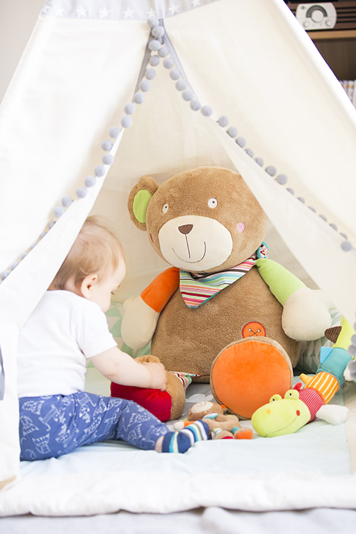 Authentische Kinderfotografie zeigt Baby beim Spielen mit einem großen Teddy in einem Zelt