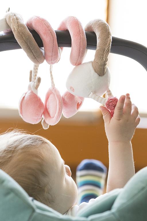 Ein Baby sitzt in einer Babyschale und greift nach einem pastellfarbenen Mobile. Dabei wurde das Baby von hinten fotografiert.