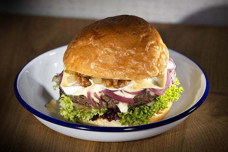 Foodaufnahme eines Burger in der Nahaufnahme – selbstgebackenes Burgerbun und geschmolzener Käse lassen den Burger sehr appetitlich wirken