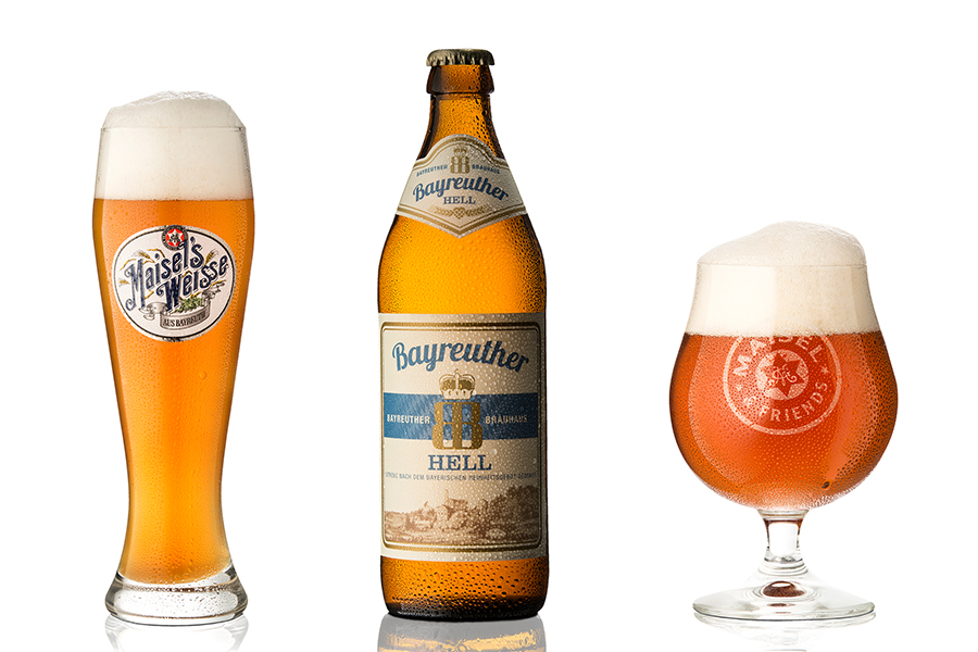 Links steht ein Weißbierglas, in der Mitte eine Flasche Bayreuther Hell und rechts ein Glas Pale Ale. Die Biere im Glas besitzen einen hervorragenden Schaum und an den Gefäßen befindet sich abperlendes Wasser.