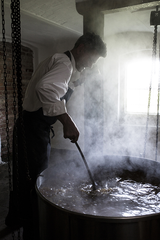 Foodfotografie zeigt Brauer Casper, der im Sudkessel rührt
