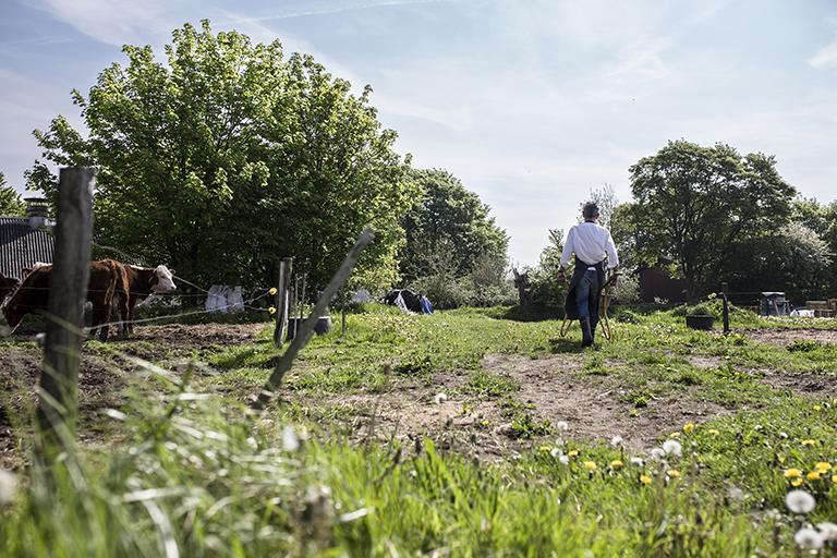 Brauer Casper schiebt einen Schubkarren über das Gelände des umgebauten Bauernhofes