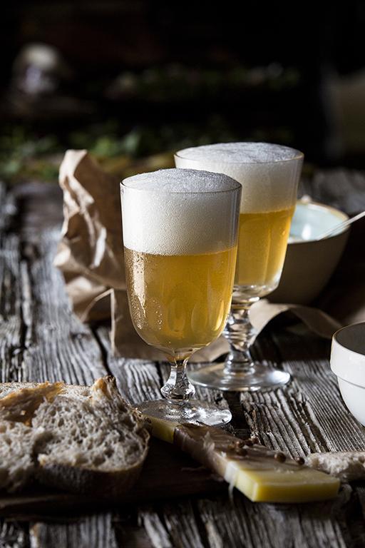 Still Life Foodfotografie: Zwei Gläser mit Bier stehen in Brotzeit-Atmosphäre auf einem alten Holztisch