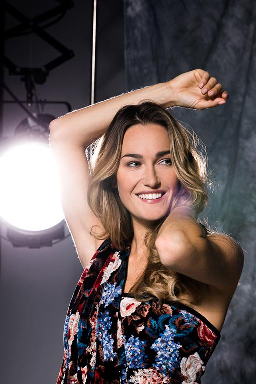 Moderne People Fotografie zeigt eine lächelnde, junge Frau mit einem FEILER-Duschtuch mit floralem Muster. Im Hintergrund wird eine Fotokulisse gekonnt inszeniert.
