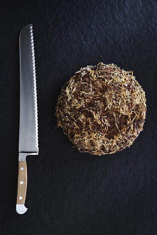 Foodfotografie mit puristischem Bildaufbau: Foto zeigt aus der Vogelperspektive das Heimatbrot und links daneben ein Brotmesser