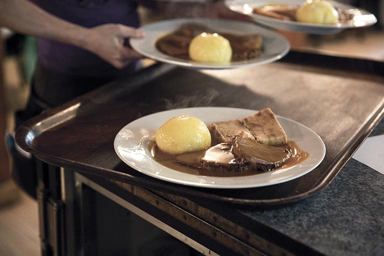 Foodfotografie zeigt ein Tablet, auf das ein Kellner mehrere Portionen dampfenden Schweinebraten stellt