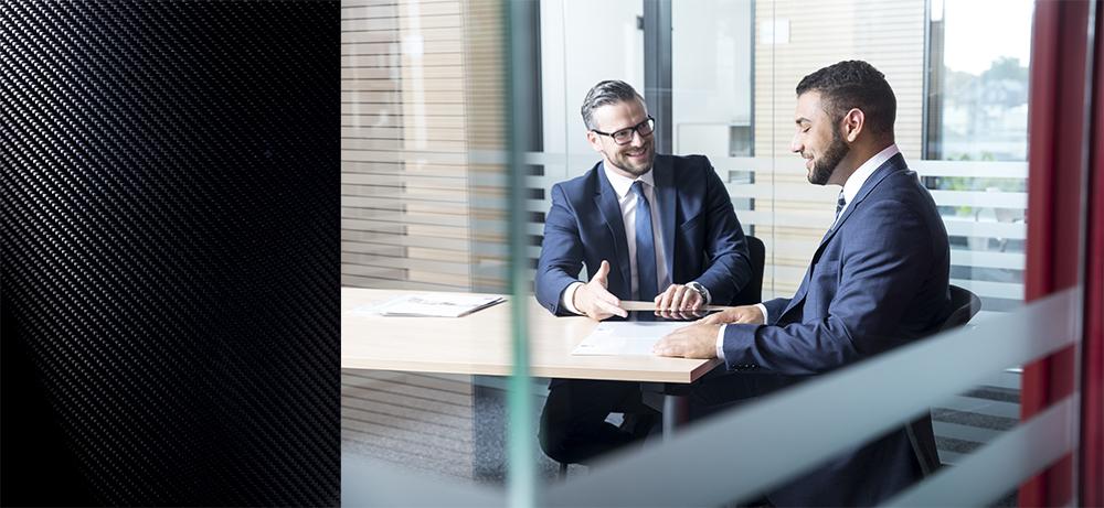 People Fotografie im rechten Bildbereich zeigt zwei Männer mit Anzug im Büro. Kombiniert wird das Bild der Arbeitssituation mit der Abbildung eines Werkstoffs im linken Bildbereich.