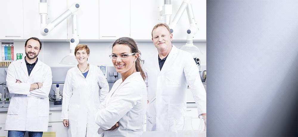 Collage aus People Fotografie und der Ansicht eines Arbeitsmaterials. Vier Mitarbeiter mit weißen Kitteln stehen lächelnd und selbstbewusst im Labor.