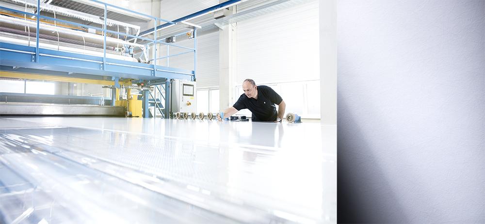 People Fotografie mit spannender Perspektive: Im rechten Bildbereich sieht man ein Material von Lamilux. Im linken Bildbereich arbeitet ein Mitarbeiter in der Produktionshalle an einem Beleuchtungssystem.