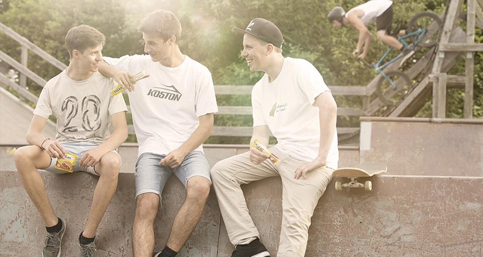 Drei junge Männer sitzen lachend im Skatepark. In den Händen halten sie produkte von Mar-Ko. I Hintergrund nimmt ein Biker Anlauf für seinen Stunt.