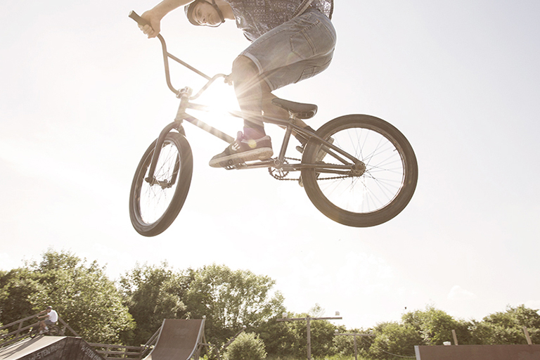 People Fotografie zeigt einen jungen Biker während eines Stunts aus der Perspektive von unten.