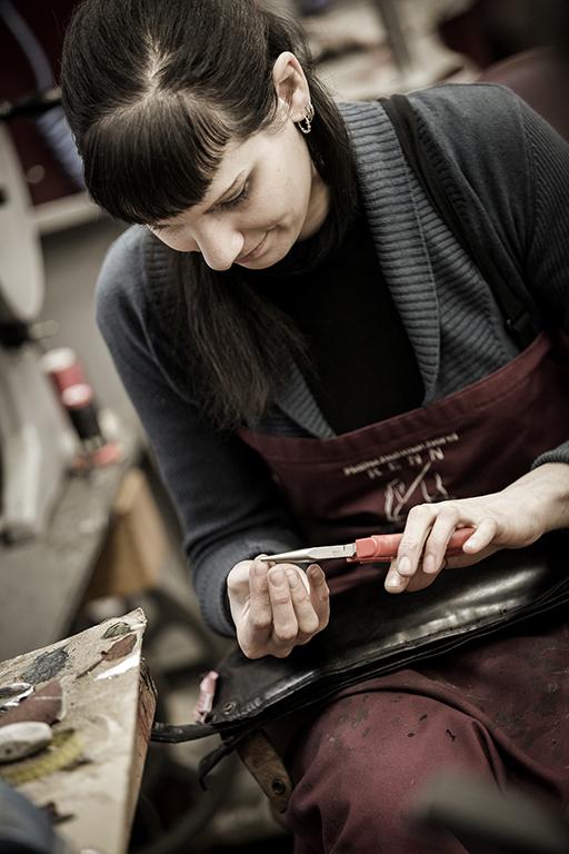 Eine junge Frau mit Pony arbeitet gerade konzentriert an einem Schuh nach Maß.