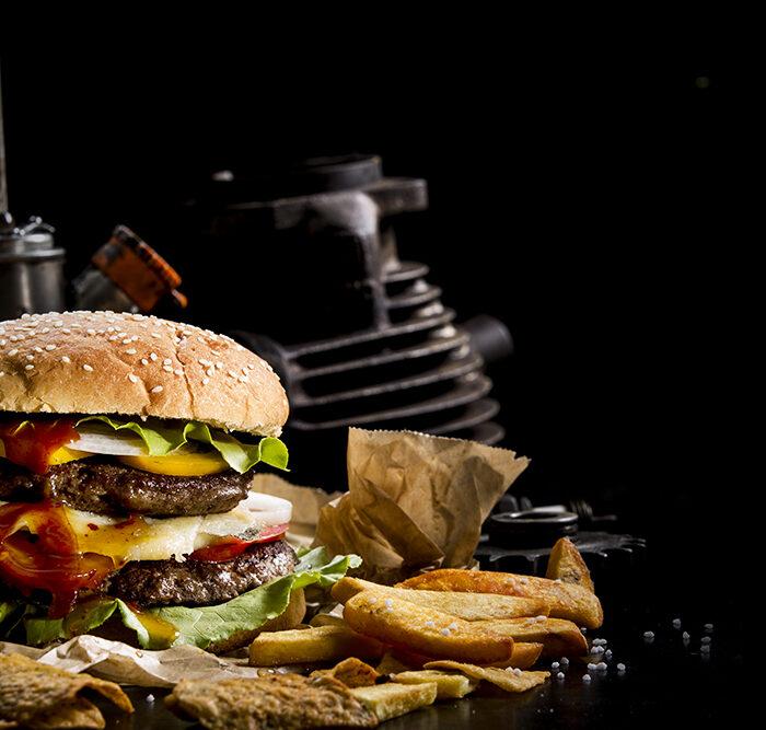 Foodfotografie zeigt einen appetitlichen, frischen Burger mit mehreren Schichten und daneben Pommes Frites