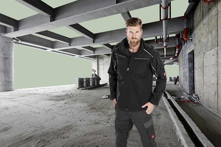 People Fotografie porträtiert einen Mann in schwarzer Rofa-Arbeitskleidung auf einer Baustelle.