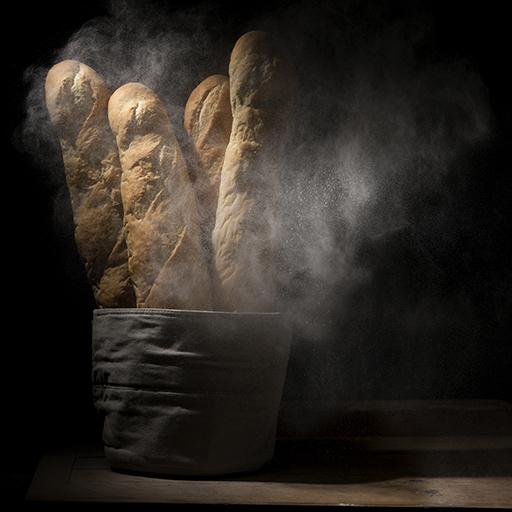 Foodaufnahmen von vier Baguettes in einem Korb mit Mehlstaub in der Luft