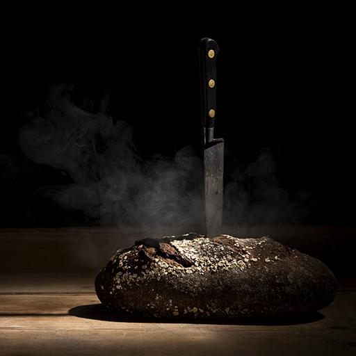 Foodaufnahme von einem Brot, in dem ein Messer steckt