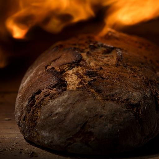 Brot von Steinofen-Meister mit Feuer im Hintergrund