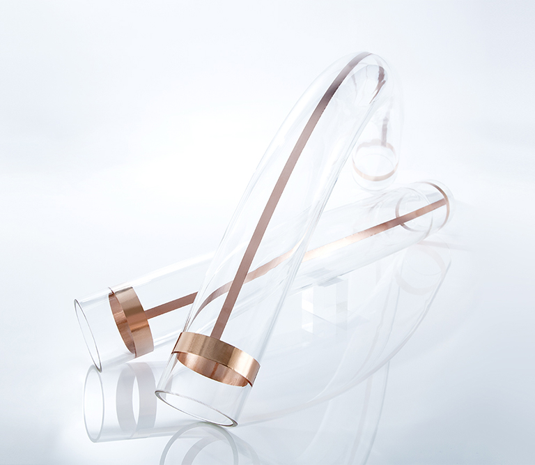 Zwei industrielle Glasröhren mit Kupfer auf weißem Untergrund ergeben ein cleanes, modernes Stillleben.