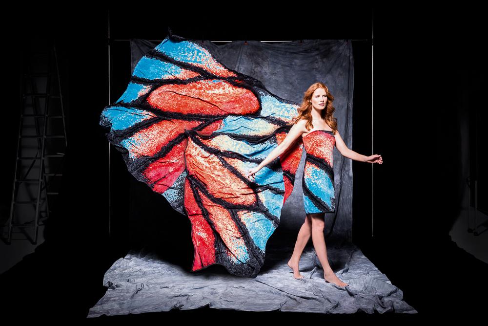 Außergewöhnliche People Fotografie zeigt eine Frau vor einer Leinwand. Sie ist mit einem rot-blauen Handtuch bekleidet, das hinter ihr weht, sodass sie wie ein Schmetterling aussieht.