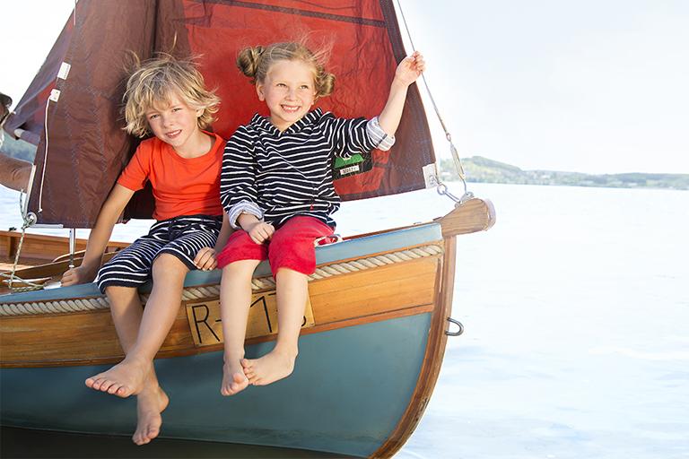 Ein Junge und ein Mädchen sitzen lachend auf einem kleinen Segelboot, das auf einem See schwimmt.