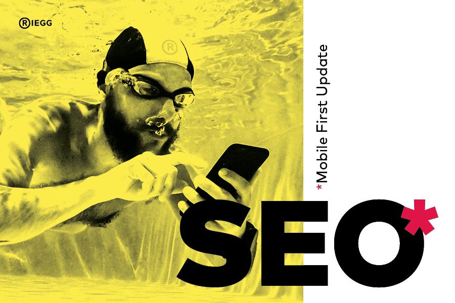 Taucher mit Schwimmbrille und Badekappe liest unter Wasser auf seinem Smartphone